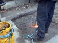 Drumarii asfaltează iarna gropile folosind butelii cu arzător